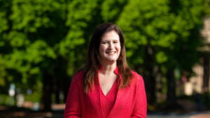 Nicole Hurd smiles on campus with a green tree behind